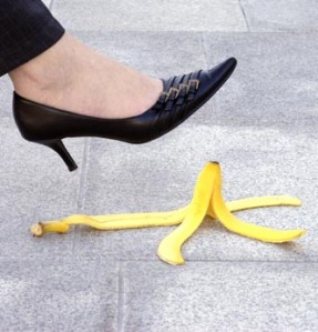 Female executive or businesswoman about to step on a banana skin