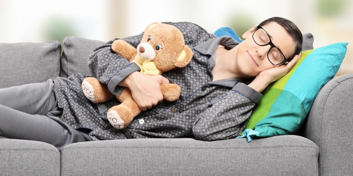 Young man in pajamas sleeping on sofa at home with teddy bear